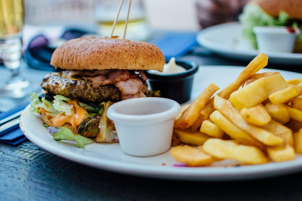 selective focus photography of burger patty, mayonnaise, and French fries served on platter