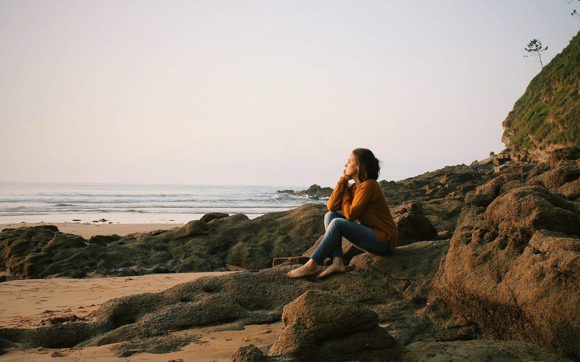woman sitting near sea during daytime