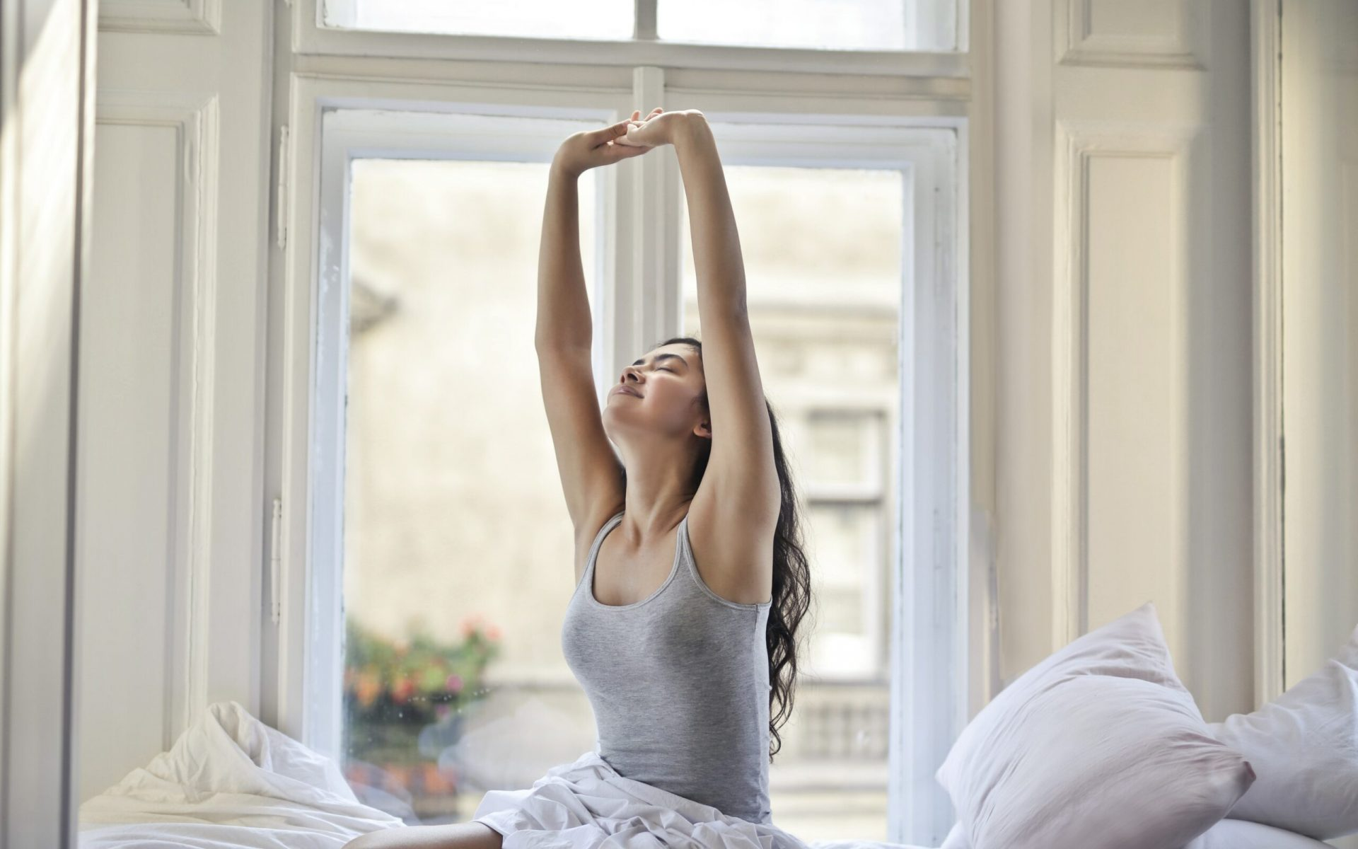 woman sitting on white bed while stretching